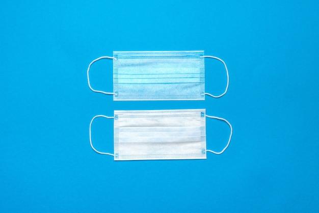 Одноразовые синие медицинские маски для лица на синем фоне