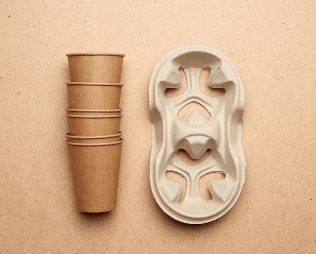 Одноразовые чашки из коричневой бумаги и держатели из переработанной бумаги на коричневом деревянном фоне