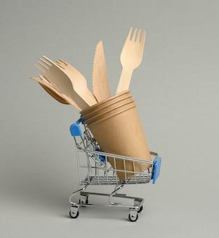 灰色の表面のミニチュア鉄のショッピングカートに使い捨ての茶色の紙コップと木製のフォーク。ゼロウェイスト