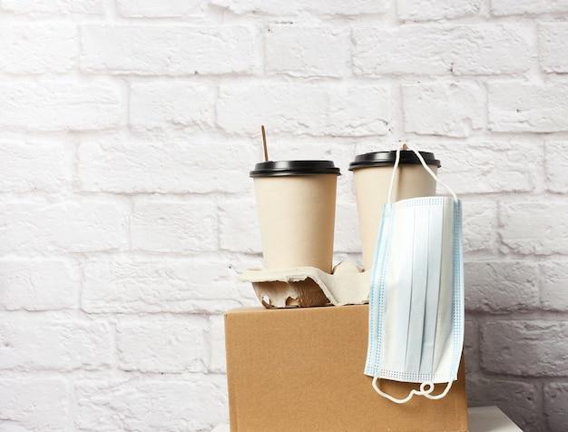 Одноразовые бумажные стаканчики из коричневой бумаги в лотке и медицинская маска