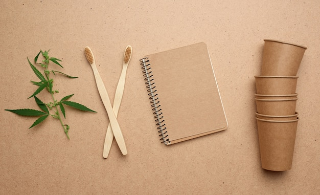Disposable brown paper cups, notepad and wooden environmental toothbrushes on a brown background, top view