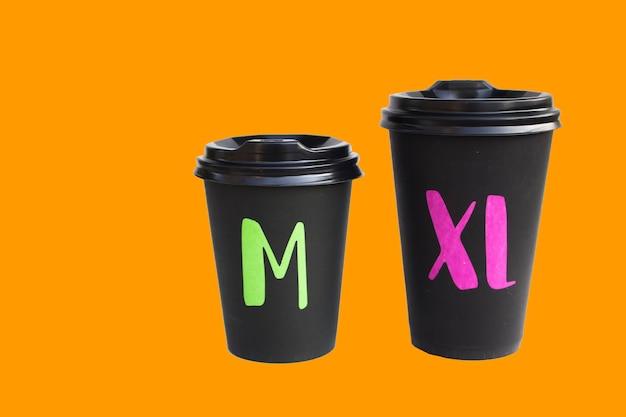 오렌지 표면, 뜨거운 음료에 대 한 에코 컵, 가을 분위기에 고립 된 일회용 골 판지 검은 컵.