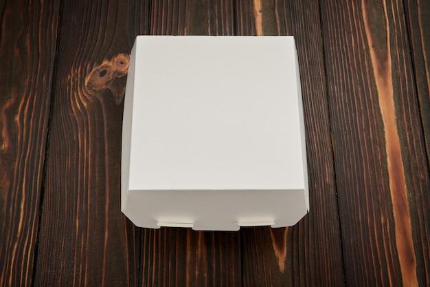 テキストのための場所と、木製の背景に食品配達のための使い捨て段ボール箱