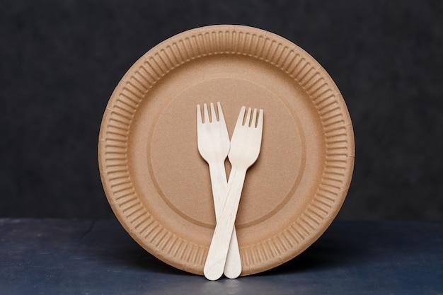 환경 친화적 인 재료로 만든 일회용 판지 접시. 자연을 막지 않습니다. 친환경, 일회용, 재활용, 퇴비화 가능한 식기. 음료용 종이컵, 접시
