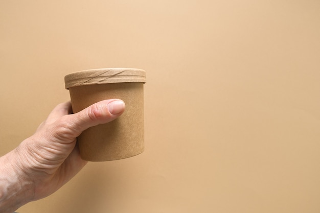 Disposable cardboard soup cup in womans hand on brown paper space with copy space