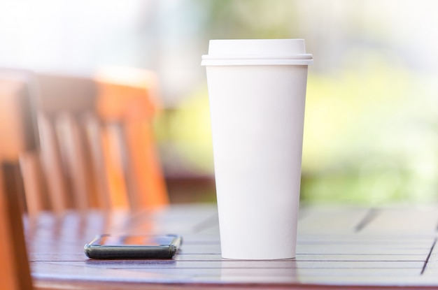Disposable coffee cup and smartphone on wooden table at cafe terrace blurred background