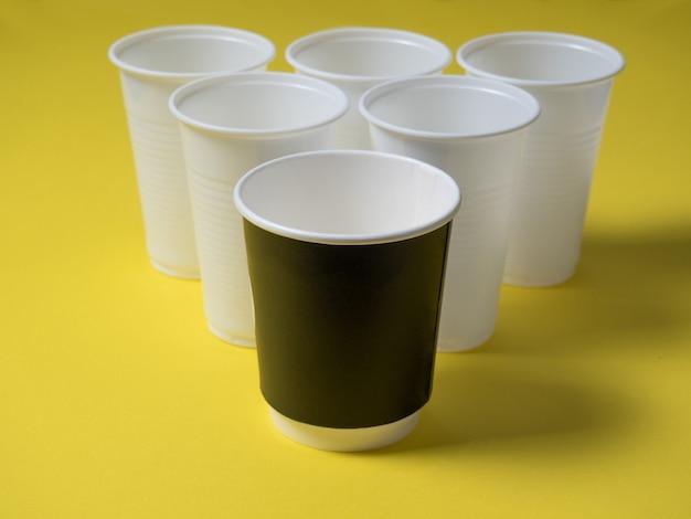 使い捨てのコーヒーカップのプラスチックと紙は黄色の背景の上に立っています。