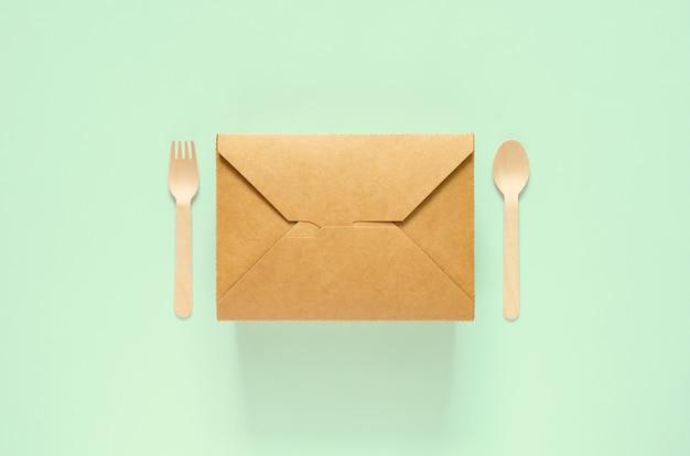 世界環境デーのコンセプトのための緑の背景に使い捨て、堆肥化可能な紙の食品ボックス、フォークとスプーン