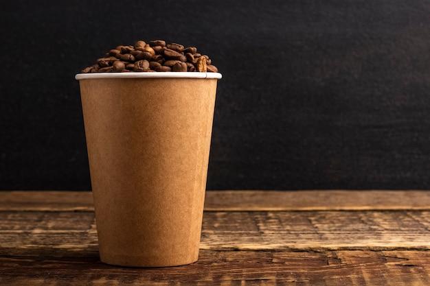 コピースペースのある木製のテーブルにコーヒーの粒が入った使い捨てのクラフトカップ。黒の背景。モックアップ