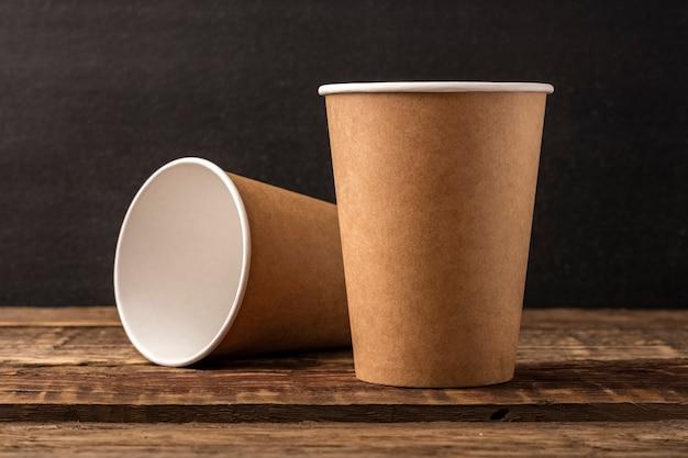 コピースペースのある木製のテーブルにクラフトから使い捨てカップ。暗い背景、モックアップ