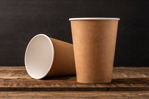 Disposable cup from craft on a wooden table with copy space. dark background, mockup