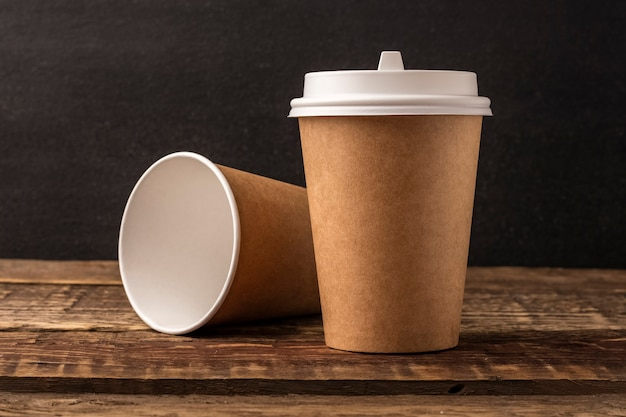 コピースペースのある木製テーブルのクラフトからの使い捨てカップ。黒の背景。モックアップ