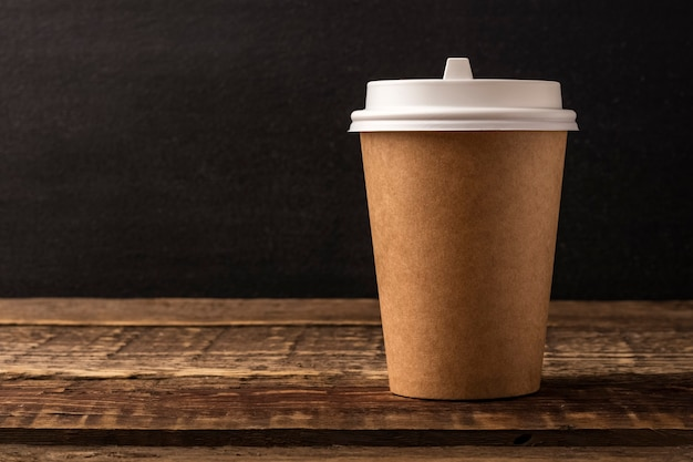 Disposable cup from kraft on a wooden table with copy space. black background. mockup