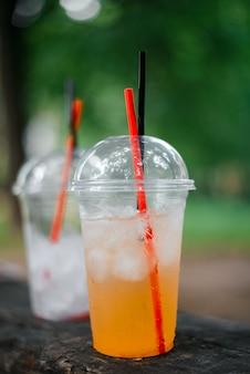 外にフレッシュジュースと氷が入った使い捨てカップ。冷たい飲み物の暑い夏のコンセプト。縦の写真
