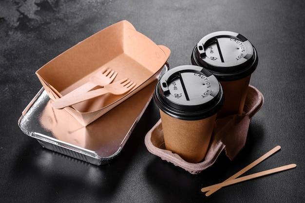暗い背景に環境にやさしい茶色のボール紙で作られた使い捨て料理。使い捨て皿での食品配達