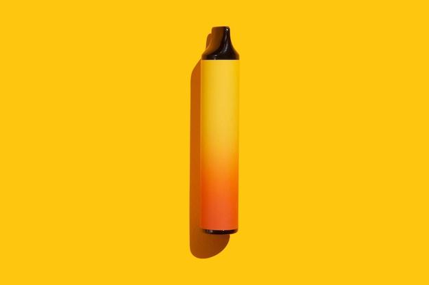 Одноразовые электронные сигареты на желтом фоне