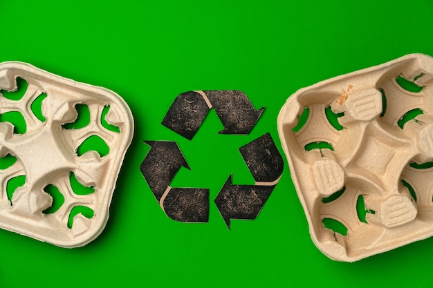 Disposable eco-friendly cardboard package on green background top view