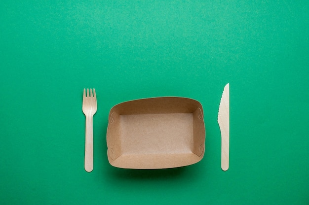 Disposable eco friendly food packaging. brown kraft paper food container with fork and knife on green background with blank space for text. top view, flat lay.