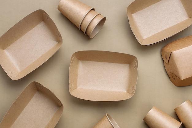 Disposable eco friendly food packaging. brown kraft paper food containers on beige background. top view, flat lay.