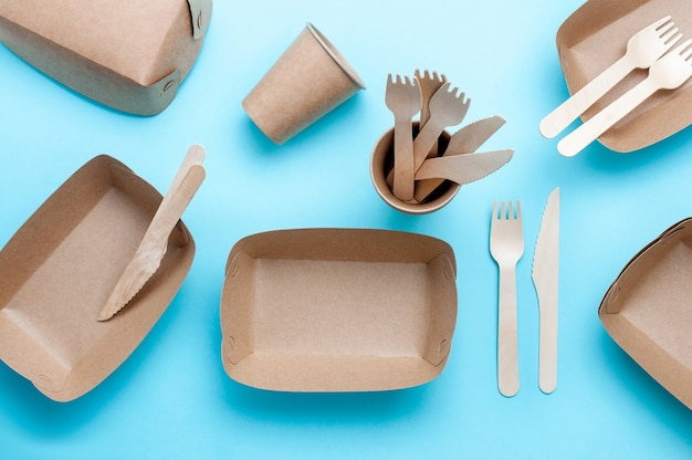 Disposable eco friendly food packaging. brown kraft paper food containers on blue background. top view, flat lay.