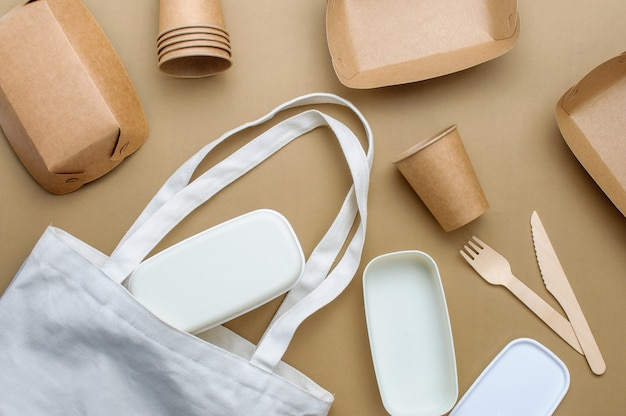 Disposable eco friendly food packaging. brown kraft paper food containers, cups and lunchbox in fabric bag on beige surface. top view, flat lay.