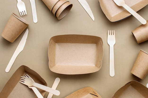 Disposable eco friendly food packaging. brown kraft paper food containers, forks and knifes on beige background. top view, flat lay.