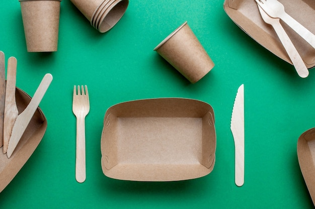 Disposable eco friendly food packaging. brown kraft paper food containers on green background. top view, flat lay.
