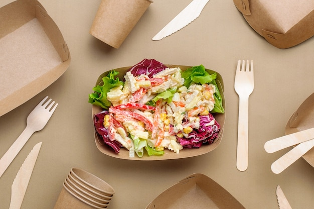 Disposable eco friendly food packaging. vegetable salad in the brown kraft paper food container on beige surface. top view, flat lay.