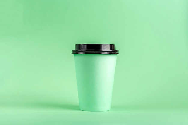 Disposable eco paper cup with coffee on green background. mockup for advertising.