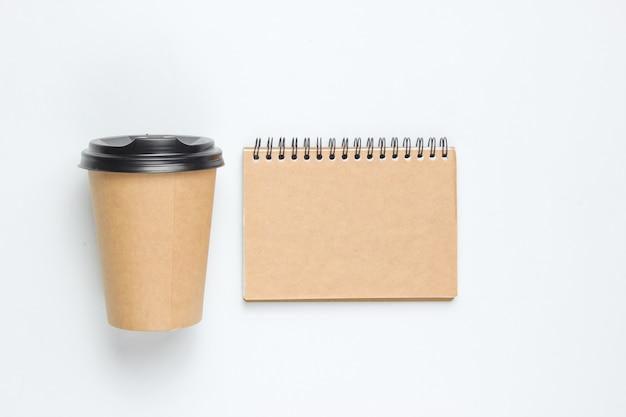 천연 재료와 공예 노트북 흰색 배경에 일회용 빈 커피 컵. 친환경 개념