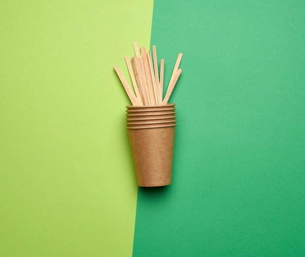 Disposable empty cups of brown craft paper and wooden sticks