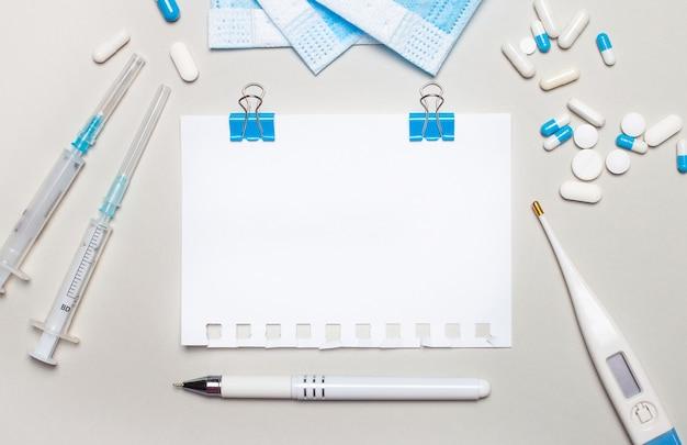 Одноразовая маска для лица, электронный термометр для тела, шприцы и рассыпанные таблетки, ручка и блокнот с местом для вставки текста на голубой поверхности