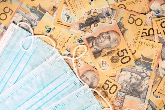 Одноразовая маска для лица на фоне австралийского доллара. концепция финансового кризиса
