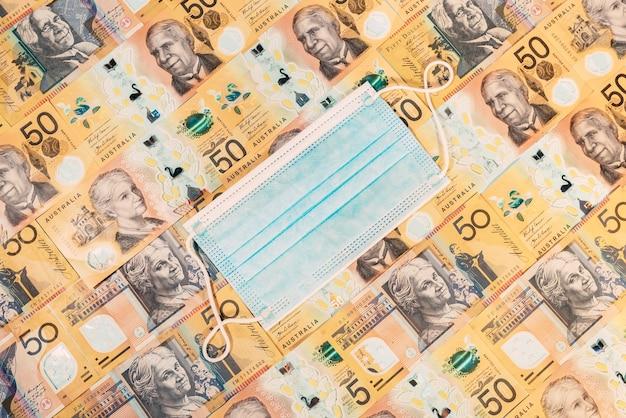 Одноразовая маска для лица на фоне австралийского доллара.