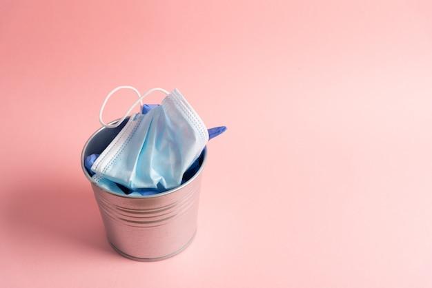 Одноразовая маска и перчатки внутри мусорного ведра на простом фоне