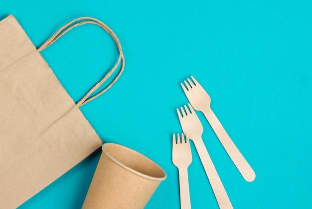 天然素材の使い捨て台所用品。環境にやさしいコンセプト。木製のフォーク、空のクラフトコーヒーカップ、青い背景のバッグ。上面図