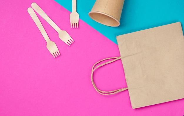 天然素材の使い捨て台所用品。環境にやさしいコンセプト。木製のフォーク、空のクラフトコーヒーカップ、ブルーピンクの背景にバッグ。上面図