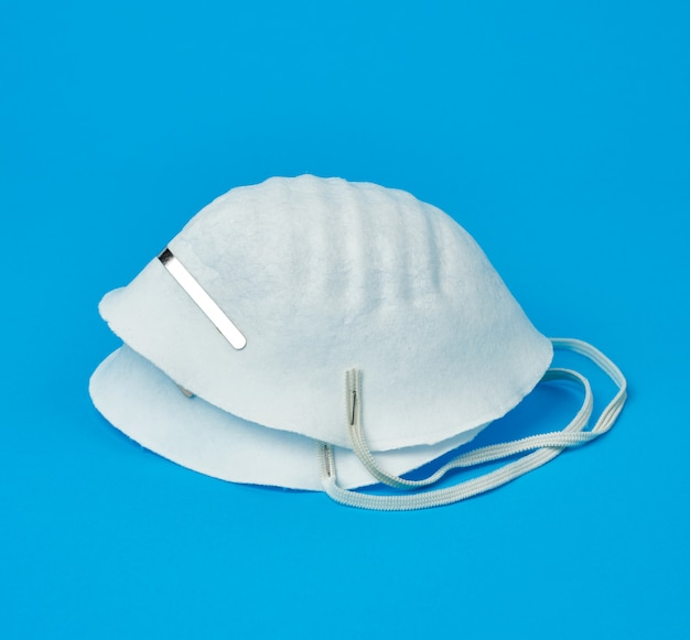Disposable masks made of non-woven material with white rubber bands on a blue background, protective accessory