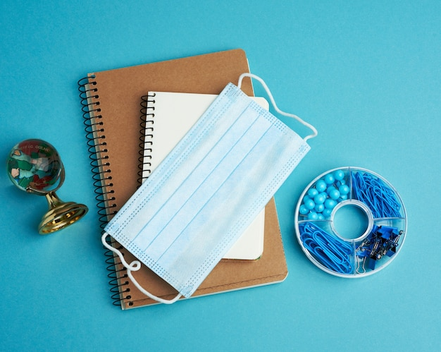 Одноразовая медицинская маска для лица и спиральный бумажный блокнот, канцелярские товары на синем