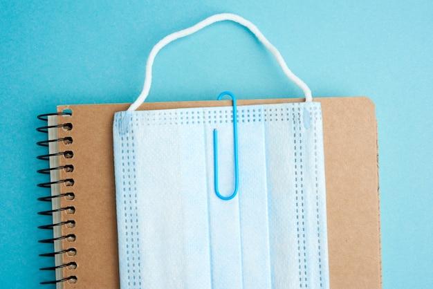 Одноразовая медицинская маска для лица и спиральный бумажный блокнот на синем фоне, концепция пандемии и обучения, снова в школу