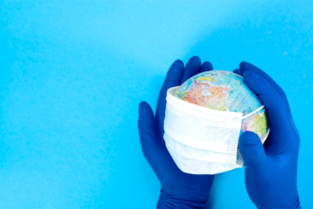 Disposable medical mask on the globe in the hands of a doctor , model of the earth. the concept of a pandemic. kovid-19, coronavirus. the global epidemic of the disease.