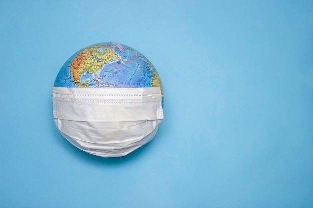 Disposable medical mask on the globe, model of the earth. the concept of a pandemic. covid-19, coronavirus. world epidemic of the disease. covid dangerous virus.