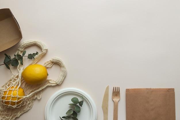 使い捨ての有機食器。ナイフ、フォーク、皿、紐袋、紙袋。ゼロウェイストとリサイクル