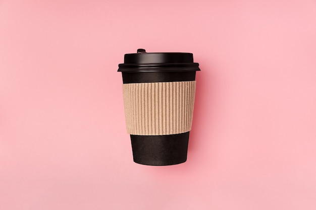 Disposable paper black cup for takeaway drink coffee which recyclable flat lay on pink backgroud