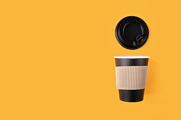 Disposable paper black cup with plastic lid for coffee flat lay on yellow background with copy space