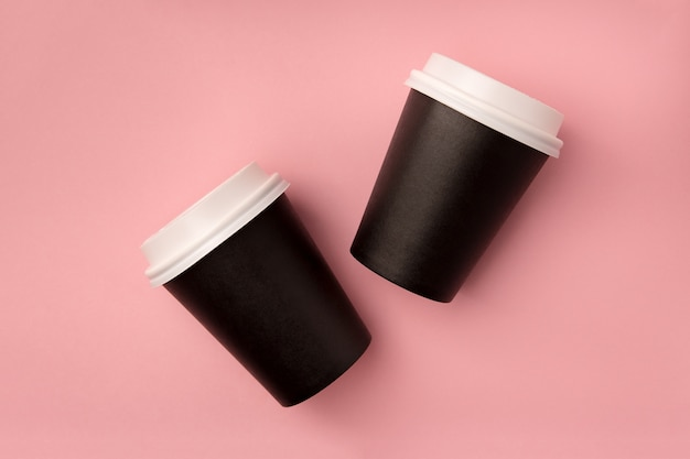 Disposable paper black cups with a closed plastic lid for coffee to go top view on pink