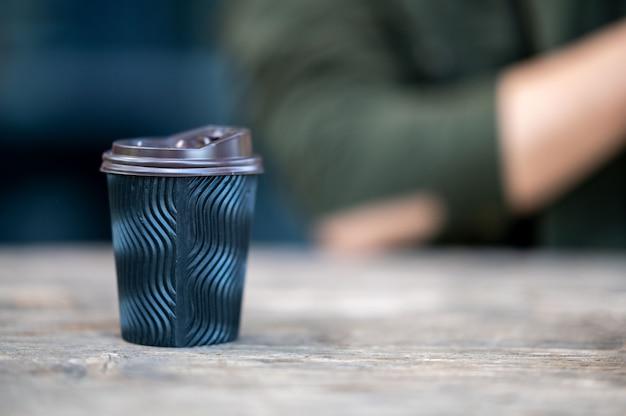 Одноразовая бумажная кофейная кружка ставится на деревянный стол для еды на вынос