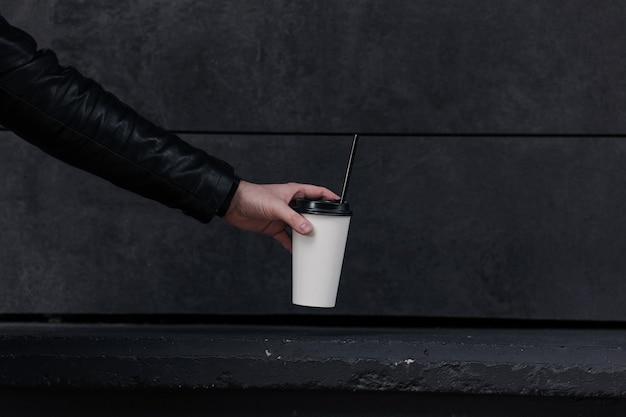 使い捨ての紙コップのコーヒー。テイクアウトコーヒーを持っている手