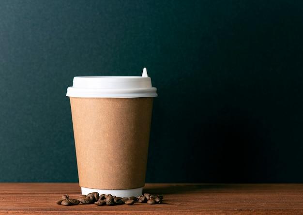 Одноразовый бумажный стаканчик с горячим кофе и жареными кофейными зернами на деревянном столе перед черной стеной. место для текста