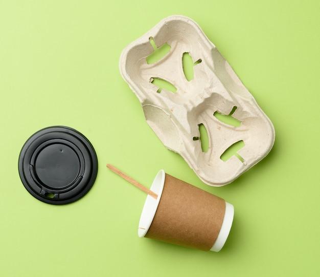Одноразовые бумажные стаканчики из коричневой крафт-бумаги и держатели из переработанной бумаги на зеленом